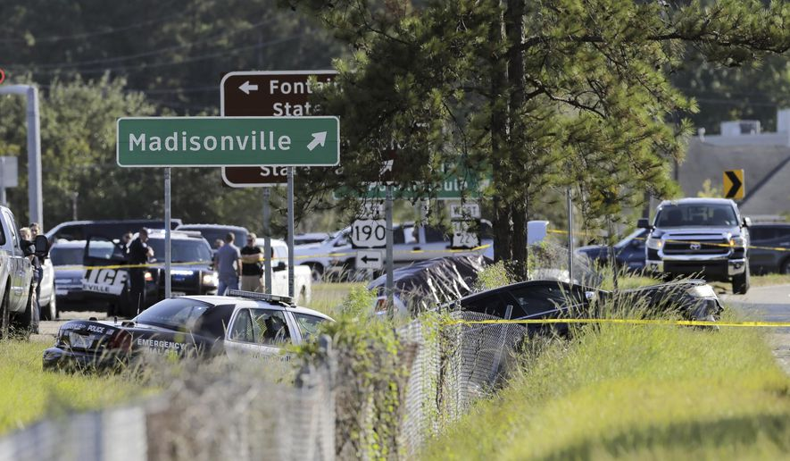 Two Mandeville police officers were shot after a vehicle chase, one fatally, near the U.S. 190 and Louisiana Highway 22 exit in Mandeville, La., Friday, Sept. 20, 2019. Mandeville Police Chief Gerald Sticker says one officer was killed and the other was wounded Friday but expected to survive the shooting in that community on the north shore of Lake Pontchartrain. Two suspects are in custody. (David Grunfeld/The Advocate via AP)