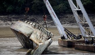 In this Tuesday, Aug. 27, 2019 photo, one of two sunken barges is removed from the Webbers Falls Lock and Dam 16. The barges broke loose up river and sunk during May's historic flooding. U.S. Sen. Jim Inhofe says an Arkansas River system that runs from Tulsa to the Mississippi River is facing a $225 million backlog of maintenance projects after being hindered for months this summer by historic flooding in Oklahoma. (Mike Simons/Tulsa World via AP)