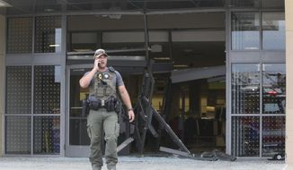 A state police officer stands outside of a Woodfield Mall entrance after a man drove an SUV into a Sears store in the Chicago suburb of Schaumburg, Ill., on Friday, Sept. 20, 2019. (John J. Kim/Chicago Tribune via AP)