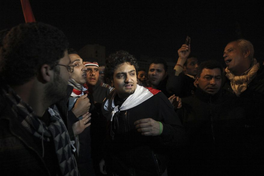 """FILE - In this Feb. 10, 2011 file photo, Egyptian Wael Ghonim, center,  walks into Tahrir Square after Egyptian President Hosni Mubarak's televised statement to his nation, in downtown Cairo, Egypt.   Ghonim said late Thursday, Sept. 19, 2019 in a video on his twitter account that authorities raided his parents' house in Cairo and arrested his brother Hazem, whom he described as """"a political person"""" and confiscated his parents' passports. Ghonim alleges that the Egyptian embassy in the U.S. threatened him the previous day """"something will happen"""" if he didn't stop criticizing Egypt's government on social media.   (AP Photo/Tara Todras-Whitehill)"""