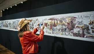 """In this photo taken Wednesday, Sept. 18, 2019, a woman takes a photo of the """"Game of Thrones"""" tapestry in Bayeux, Normandy, France. The """"Game of Thrones"""" tapestry depicts major scenes from all eight seasons of the hit TV series in 87 meters of embroidery. The artwork is temporarily on display in Bayeux, the Normandy town famous for the 11th century Bayeux tapestry chronicling the Norman conquest of England. """"Game of Thrones"""" is expected to rack up more awards at the Emmy ceremony on Sunday. (AP Photo/Kamil Zihnioglu)"""