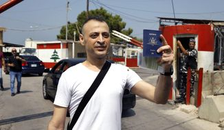 Australian-Lebanese dual citizen Amer Khayyat stands as he holds his Australian passport, after his release from prison in Roumieh, east of Beirut, Lebanon, Friday, Sept. 20, 2019. Lebanese authorities have released the Lebanese -Australian who had been detained in Lebanon for more than two years after he was found innocent in an alleged plot to bring down a passenger plane bound for the United Arab Emirates from Sydney. (AP Photo/Bilal Hussein)