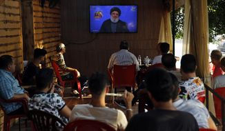 FILE - This Sunday Aug. 25, 2019 file photo, people listen to a speech by Hezbollah leader Sayyed Hassan Nasrallah being broadcast on Hezbollah's al-Manar TV channel, at a coffee shop in a southern suburb of Beirut, Lebanon. Nasrallah has called Friday, Sept. 20, 2019 on Saudi Arabia to stop the war in Yemen otherwise it will face more attacks on its soil. (AP Photo/Bilal Hussein, File)