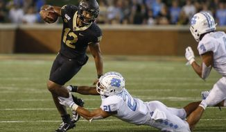 Wake Forest quarterback Jamie Newman (12) breaks away from North Carolina linebacker Chazz Surratt (21) during the second half of an NCAA college football game in Winston-Salem, N.C., Friday, Sept. 13, 2019. Wake Forest won 24-18. (AP Photo/Nell Redmond)