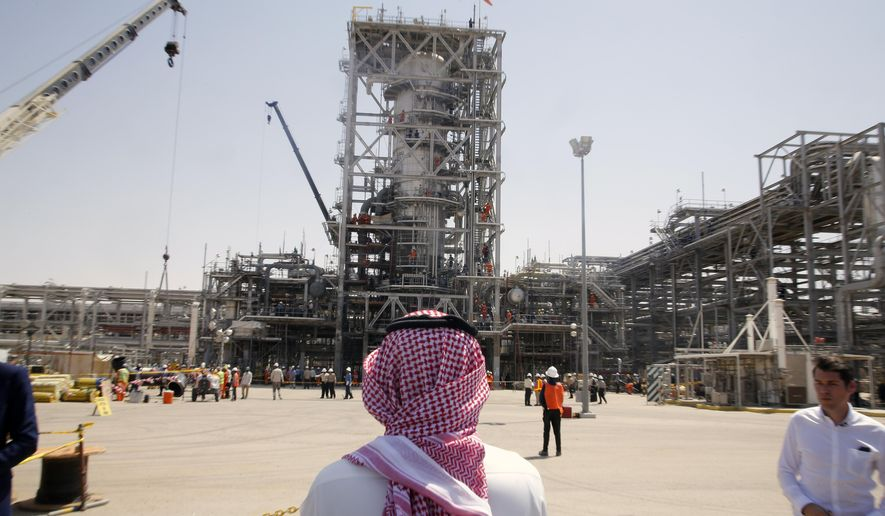 In this photo opportunity during a trip organized by Saudi information ministry, a man stands in front of the Khurais oil field in Khurais, Saudi Arabia, Friday, Sept. 20, 2019, after it was hit during Sept. 14 attack. Saudi officials brought journalists Friday to see the damage done in an attack the U.S. alleges Iran carried out. Iran denies that. Yemen's Houthi rebels claimed the assault. (AP Photo/Amr Nabil)