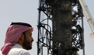 In this photo opportunity during a trip organized by Saudi information ministry, a man watches the damaged in the Aramco's Khurais oil field, Saudi Arabia, Friday, Sept. 20, 2019, after it was hit during Sept. 14 attack. Saudi officials brought journalists Friday to see the damage done in an attack the U.S. alleges Iran carried out. (AP Photo/Amr Nabil)