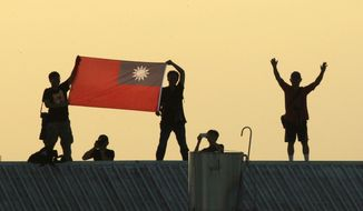 In this Sept. 14, 2014, file photo, locals on a warehouse rooftop display the national flag while watching Taiwan fighter jets practice during military exercises in Chiayi, central Taiwan. Taiwan reported on Sept. 18 that China had sent 18 planes into its airspace defense identification zone, prompting the island nation to scramble fighter jets and put its air-defense system on alert. (AP Photo/Wally Santana, File) **FILE**
