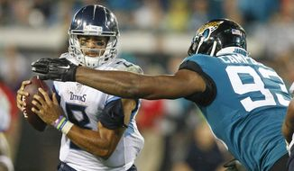Tennessee Titans quarterback Marcus Mariota, left, looks to dodge a tackle by Jacksonville Jaguars defensive end Calais Campbell (93) during the second half of an NFL football game, Thursday, Sept. 19, 2019, in Jacksonville, Fla. (AP Photo/Stephen B. Morton)