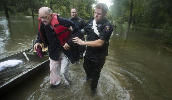 Fred Stewart, left, is helped to high ground by Splendora Police officer Mike Jones after he was rescued from his flooded neighborhood as rains from Tropical Depression Imelda inundated the area, Thursday, Sept. 19, 2019, in Splendora, Texas. (Brett Coomer/Houston Chronicle via AP)