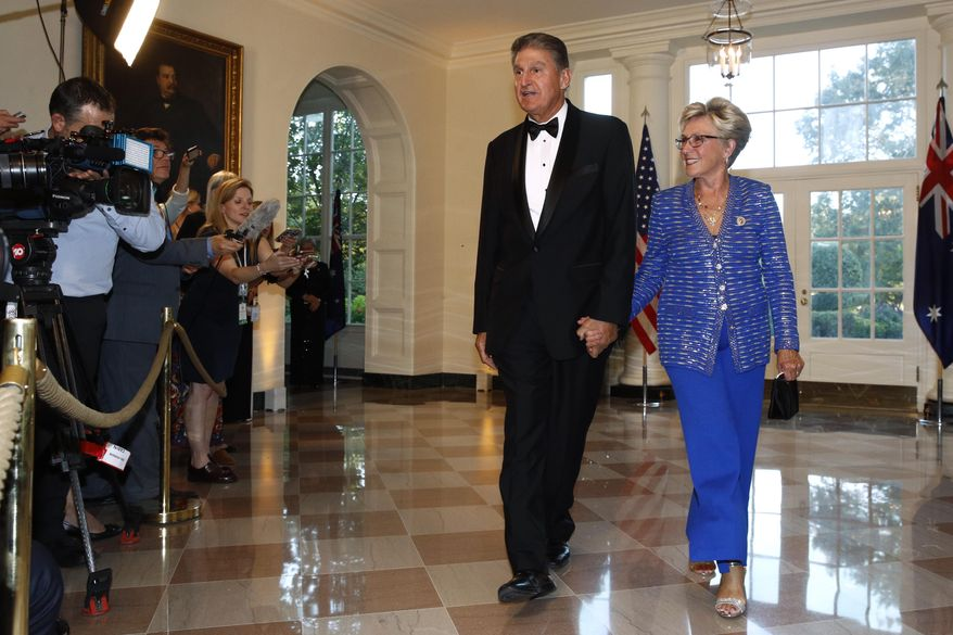 Sen. Joe Manchin, D-W.Va., left, and wife Gayle Conelly Manchin arrive for a State Dinner with Australian Prime Minister Scott Morrison and President Donald Trump at the White House, Friday, Sept. 20, 2019, in Washington. (AP Photo/Patrick Semansky)