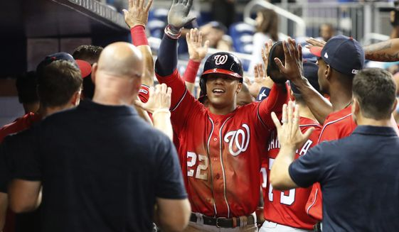 Washington Nationals' Juan Soto (22) is congratulated by teammates after he, Adam Eaton and Anthony Rendon scored on a double by Kurt Suzuki during the 10th inning of a baseball game against the Miami Marlins, Saturday, Sept. 21, 2019, in Miami. The Nationals defeated the Marlins 10-4 in 10 innings. (AP Photo/Wilfredo Lee) ** FILE **