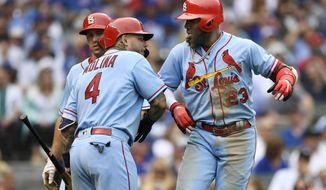 St. Louis Cardinals' Marcell Ozuna, right, celebrates with teammates Yadier Molina, left, and Paul Goldschmidt, center, after hitting a two-run home run during the seventh inning of baseball game against the Chicago Cubs Saturday, Sept. 21, 2019, in Chicago. (AP Photo/Paul Beaty)