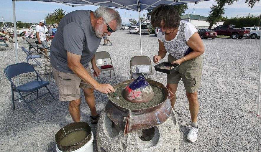 In This Sept. 13, 2019 photo, Rick and Joyce Deal decorate a concrete ball that contains the cremated remains of a loved one at the Pensacola Shipyard in Pensacola, Fla. Eternal Reefs, an Atlanta-based company, provides the opportunity for people to mix their loved ones cremated remains into concrete balls which are then placed in the Atlanta Ocean or the Gulf of Mexico. The balls become habitats for marine life. (Jody Link/Pensacola News Journal via AP)