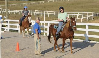 """In this Sept. 9, 2019 photo, volunteer Tom Pike coaches Mike Kerns, 13, riding """"George"""" and Timmy Kerns, 11, riding """"DJ"""" in the practice arena at Horses With Hearts in Martinsburg, W.Va. (Ron Agnir/The Journal via AP)"""