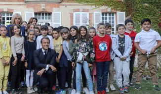 French President Emmanuel Macron, center, and his wife Brigitte Macron, left, pose for a picture with pupils visiting the Chateau de By, the former property of the late French artist Rosa Bonheur, Friday Sept. 20, 2019, in Thomery, outside Paris to launch the European Heritage Days. (Ludovic Marin, Pool via AP)