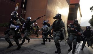 Police run during a confrontation with protesters Saturday, Sept. 21, 2019, Hong Kong. Demonstrators have marched through an outlying district of Hong Kong in another weekend of protest aimed at the Chinese territory's government. (AP Photo/Vincent Yu)