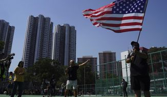 """An anti-government protester waves the U.S. flag before the start of the rally """"Reclaim Tuen Mun"""" in Tuen Mun district, in Hong Kong, Saturday, Sept. 21, 2019. Demonstrators are protesting against mainland Chinese singers causing a nuisance in the local neighborhood. (AP Photo/Vincent Yu)"""