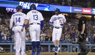 Los Angeles Dodgers' A.J. Pollock scores after hitting a three-run home run against the Colorado Rockies, as Enrique Hernandez, left, and Max Muncy, second from left, wait for him while home plate umpire Greg Gibson stands at the plate during the fourth inning of a baseball game Friday, Sept. 20, 2019, in Los Angeles. (AP Photo/Mark J. Terrill)