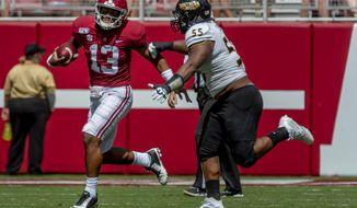 Alabama quarterback Tua Tagovailoa (13) runs the ball past Southern Miss defensive lineman Demarrio Smith (55) during the first half of an NCAA college football game, Saturday, Sept. 21, 2019, in Tuscaloosa, Ala. (AP Photo/Vasha Hunt)