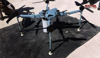 In this photo released by the Syrian official news agency SANA, shows a drone which the Syrian state news agency says authorities have controlled and dismantled was rigged with cluster bombs on the edge of the Israeli-occupied Golan Heights, southern Syria, Saturday, Sept. 21, 2019. (SANA via AP)