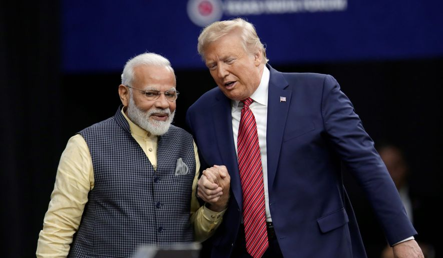 """Prime Minister Narendra Modi and President Trump shake hands after introductions during the """"Howdy Modi"""" rally Sunday in Houston. (Associated Press)"""