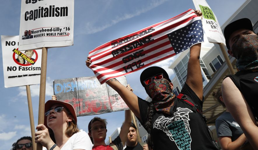 Demonstrators march past police during the Shut Down Trump & the RNC protest on Sunday, July 17, 2016, in Cleveland. The Republican National Convention starts Monday. (AP Photo/John Minchillo)