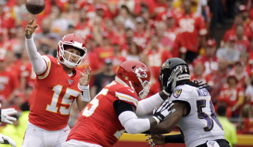 Kansas City Chiefs quarterback Patrick Mahomes (15) throws a pass as offensive tackle Cam Erving (75) blocks Baltimore Ravens linebacker Tim Williams (56) during the first half of an NFL football game in Kansas City, Mo., Sunday, Sept. 22, 2019. (AP Photo/Charlie Riedel)