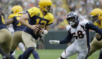 Green Bay Packers quarterback Aaron Rodgers (12) rolls out as as Denver Broncos outside linebacker Von Miller (58) rushes during the first half of an NFL football game Sunday, Sept. 22, 2019, in Green Bay, Wis. (AP Photo/Mike Roemer)