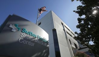 In this Friday, Sept. 20, 2019, photo, an American flag flutters in the breeze outside of the Sutter Medical Center in Sacramento, Calif. California Attorney General Xavier Becerra, along with 1,500 self-funded health plans, have sued Sutter Health for anti-trust violations. Jury selection in the trial is set to begin Monday, Sept. 23, 2019. (AP Photo/Rich Pedroncelli)