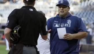 San Diego Padres interim manager Rod Barajas, right, meets with home plate umpire Alex Tosi before a baseball game against the Arizona Diamondbacks in San Diego, Saturday, Sept. 21, 2019. (AP Photo/Alex Gallardo)