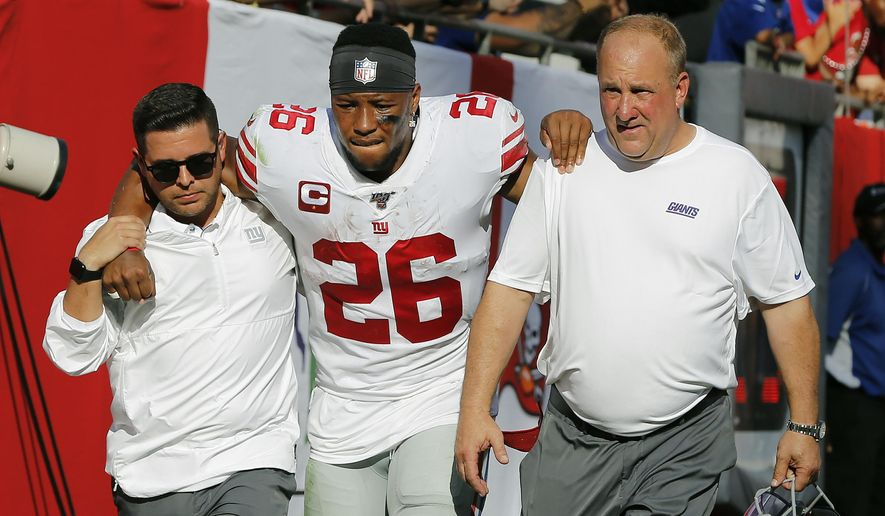 New York Giants running back Saquon Barkley (26) gets helped off the field after getting hurt against the Tampa Bay Buccaneers during the first half of an NFL football game Sunday, Sept. 22, 2019, in Tampa, Fla. (AP Photo/Mark LoMoglio)