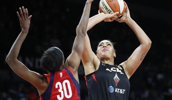 Washington Mystics' LaToya Sanders, left, fouls Las Vegas Aces' Liz Cambage during the first half in Game 3 in a semifinal game in the WNBA playoffs, Sunday, Sept. 22, 2019, in Las Vegas. (AP Photo/John Locher)