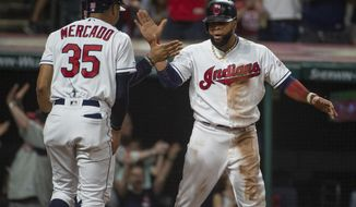 Cleveland Indians' Oscar Mercado, left, celebrates with Carlos Santana after they scored on a thee-run double by Yasiel Puig off Philadelphia Phillies relief pitcher Cole Irvin during the seventh inning of a baseball game in Cleveland, Sunday, Sept. 22, 2019. (AP Photo/Phil Long)