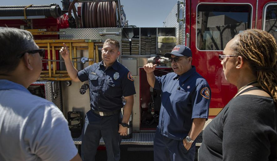 In this photo taken June 9, 2019, Los Angeles County firefighter Salvador Mejia, left, and Luis Gonzales, a Community Emergency Response Team instructor with the fire department, talk to CERT participants Berwyn Salazar and Frances Roberts in Carson, Calif. CERT training teaches members of the public how to begin helping their neighbors before professional first responders can arrive on scene. As police and firefighter numbers dwindle, authorities urge personal responsibility. (Brigette Waltermire/News21 via AP)