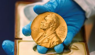 In this file photo dated Friday, April 17, 2015, a national library employee shows the gold Nobel Prize medal awarded to the late novelist Gabriel Garcia Marquez, in Bogota, Colombia. There is no bigger international honor than the Nobel Prize, created by 19th-century Swedish industrialist Alfred Nobel. (AP Photo/Fernando Vergara, FILE)
