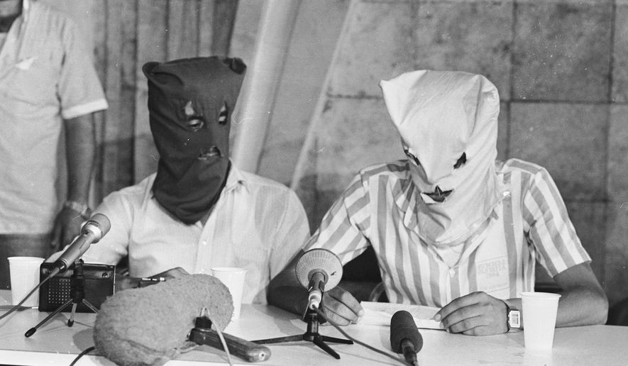 Two hooded Shiite Muslim men, who were identified as the original hijackers of the TWA jet seized on a flight from Athens to Rome on July 14 and commandeered to Beirut airport, hold a news conference at the Beirut airport's transit terminal,July 30, 1985. (AP Photo)