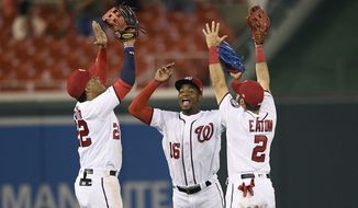 Washington Nationals' Juan Soto, left, Victor Robles, center, and Adam Eaton, right, celebrate after a baseball game against the Philadelphia Phillies, Monday, Sept. 23, 2019, in Washington. (AP Photo/Nick Wass)
