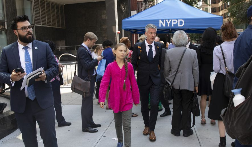 Greta Thunberg, center, walks with an entourage after passing a security checkpoint while appearing at the United Nations, Monday, Sept. 23, 2019 in New York. (AP Photo/Mark Lennihan)