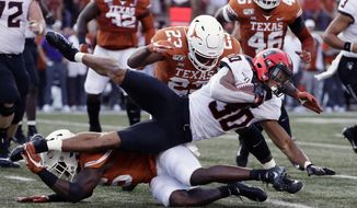Oklahoma State running back Chuba Hubbard (30) is stopped by Texas defensive lineman Peter Mpagi, bottom, and linebacker Jeffrey McCulloch (23) during the first half of an NCAA college football game Saturday, Sept. 21, 2019, in Austin, Texas. (AP Photo/Eric Gay)