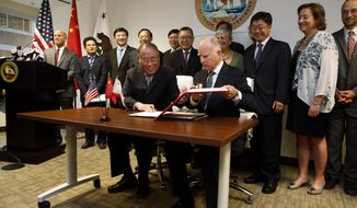 FILE - In this Sept. 13, 2014, file photo, California Gov. Jerry Brown, front right, and China's National Development and Reform Commission Vice Chairman Xie Zhenhua, front left, sign an agreement to boost bilateral cooperation on climate change during a news conference at the Bay Area Council, in San Francisco. As tensions between China and the United States ratchet up, former California Gov. Jerry Brown sees a way to bring together the world's largest carbon emitter and a U.S. state that's leading the way in energy standards: climate change. (AP Photo/Beck Diefenbach,file)