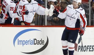 FILE - In this March 15, 2018, file photo, Washington Capitals center Nicklas Backstrom (19), of Sweden, is congratulated by right wing Devante Smith-Pelly (25) and goaltender Braden Holtby (70) after scoring during the second period of an NHL hockey game against the New York Islanders, in New York. The Washington Capitals are still a Stanley Cup contender a year removed from raising their first title banner in franchise history. (AP Photo/Kathy Willens, File)