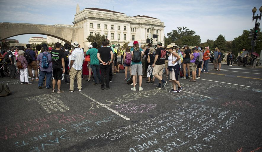 Chesapeake Climate Action Network Action Fund members block traffic along Independence Avenue and 12th Street Southwest near the National Mall in Washington, Monday, Sept. 23, 2019. A broad coalition of climate and social justice organizations are disrupting the morning rush hour commute. (AP Photo/Andrew Harnik)