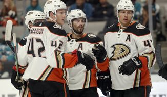 FILE - In this Tuesday, Sept. 17, 2019, file photo, Anaheim Ducks center Adam Henrique, middle, gathers with teammates after scoring a goal against the San Jose Sharks during an NHL preseason hockey game in San Jose, Calif. Henrique is one of several veteran forwards returning to the Ducks this fall after they missed the playoffs for the first time in seven seasons. Anaheim is hoping for a quick return to playoff contention under new coach Dallas Eakins. (AP Photo/Jeff Chiu, File)