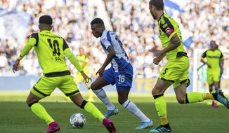 In this Saturday, Sept. 21, 2019 photo, Berlin's Javairo Dilrosun, center, challenges for the ball with Paderborn's Cauly Oliveira Souza, left, and Christian Strohdiek, right, during the German Bundesliga soccer match between Hertha BSC Berlin and SC Paderborn 07, at the Olympic Stadion in Berlin. ( Soeren Stache/dpa via AP)