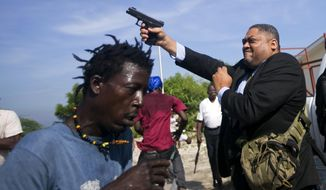 Ruling party Senator Ralph Fethiere fires his gun outside Parliament as he arrives for a vote on the ratification of Fritz William Michel's nomination as prime minister in Port-au-Prince, Haiti, Monday, Sept. 23, 2019. Opposition members confronted ruling-party senators, and Fethiere pulled a pistol when protesters rushed at him and members of his entourage. The vote was cancelled. (AP Photo/Dieu Nalio Chery)