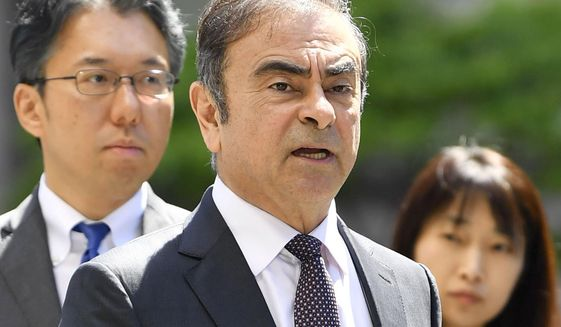 FILE - In this May 23, 2019, file photo former Nissan chairman Carlos Ghosn, center, arrives at Tokyo District Court for a pre-trial meeting in Tokyo.  Nissan has agreed to pay $15 million and its former chairman Carlos Ghosn is paying $1 million to settle federal regulators' civil fraud charges of hiding from investors more than $140 million in compensation and retirement benefits for Ghosn. (Ren Onuma/Kyodo News via AP, File)