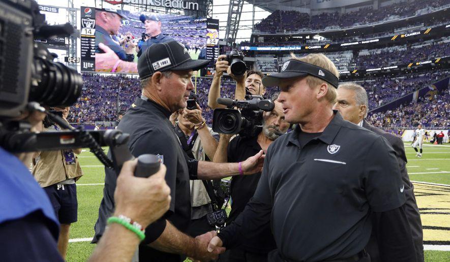 Minnesota Vikings head coach Mike Zimmer, left, talks with Oakland Raiders head coach Jon Gruden after an NFL football game, Sunday, Sept. 22, 2019, in Minneapolis. The Vikings won 34-14. (AP Photo/Bruce Kluckhohn)
