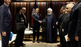 In this photo released by the official website of the office of the Iranian Presidency, President Hassan Rouhani, right, shakes hands with French President Emmanuel Macron during their meeting on the sideline of the United Nations General Assembly at U.N. headquarters, Tuesday, Sept. 24, 2019. (Iranian Presidency Office via AP)