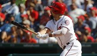 Washington Nationals' Anthony Rendon hits a sacrifice fly ball in the sixth inning of the first baseball game of a doubleheader against the Philadelphia Phillies, Tuesday, Sept. 24, 2019, in Washington. Trea Turner scored on the play. (AP Photo/Patrick Semansky)