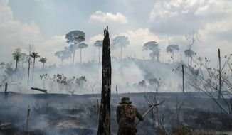 FILE - In this Sept. 3, 2019, file photo, Brazilian soldier puts out fires at the Nova Fronteira region in Novo Progresso, Brazil.  The fires that swept parts of the Amazon this year added to global worries about a warming climate, as well as the sense of urgency at the Climate Action Summit at the United Nations. (AP Photo/Leo Correa, File)